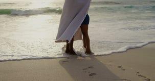 Seitenansicht von den Afroamerikanerpaaren eingewickelt in der Decke auf dem Strand 4k stock video footage