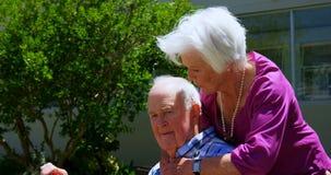 Seitenansicht von den aktiven kaukasischen älteren Paaren, die im Garten des Pflegeheims 4k sich umfassen stock video