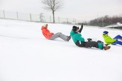 Seitenansicht von den jungen Freunden, die auf Schnee sledging sind, umfasste Steigung Stockbild
