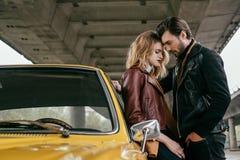 Seitenansicht von den stilvollen jungen Paaren, die darunter nahe gelbem Retro- Auto umarmen stockfotografie