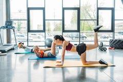 Seitenansicht von drei multiethnischen weiblichen Athleten, die auf Eignungsmatten trainieren stockfoto