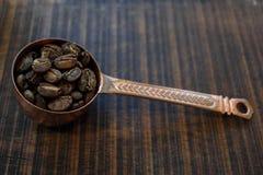 Seitenansicht von Kaffeebohnen innerhalb des kupfernen Löffels an hölzernem BAC der Unschärfe Lizenzfreies Stockfoto