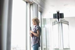 Seitenansicht von kreativen Geschäftsfrauholdingdateien beim Schauen durch Fenster im Büro Stockfotografie