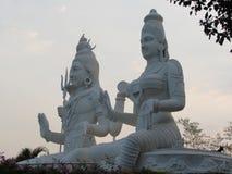 Seitenansicht von Lord shiva mit dem parvati, das Abend am indischen Park ehrfürchtig betrachtet lizenzfreie stockfotos