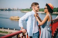 Seitenansicht von zwischen verschiedenen Rassen stilvollen Paaren in der Sonnenbrille, die vorbei auf Brücke steht stockfotografie