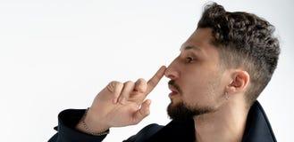 Seitenansichtabschlu? herauf Portr?t des jungen b?rtigen Mannes das, der seine Nase mit dem Finger lokalisiert ?ber wei?em Hinter lizenzfreies stockbild