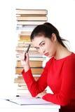 Seitenansichtfrau, die mit Stapel Büchern sitzt Stockbilder