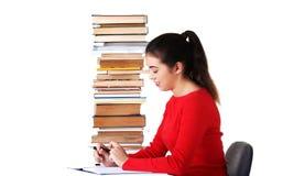Seitenansichtfrau, die mit Stapel Büchern sitzt Stockfotos