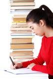 Seitenansichtfrau, die mit Stapel Büchern sitzt Stockfotografie