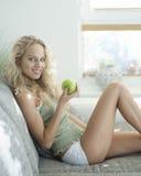 Seitenansichtporträt der jungen Frau Apfel beim Sitzen halten auf Sofa im Haus Lizenzfreie Stockfotografie