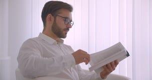 Seitenansichtporträt der Nahaufnahme des erwachsenen hübschen kaukasischen Geschäftsmannes in den Gläsern ein Buch lesend, das he stock video