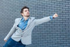 Seitenansichtporträt des Profils des ernsten hübschen bärtigen Mannes in der Stellung der zufälligen Art in der Supermanngeste mi lizenzfreie stockfotos