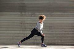 Seitenansichtporträt einer jungen Frau, die Bein ausdehnt, mischt mit Stockfoto