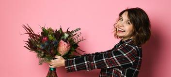Seitenansichtprofil der attraktiven jungen Frau in einem dunklen karierten dresst, das Blumenstrauß von Blumen hält und Sie gibt lizenzfreies stockfoto