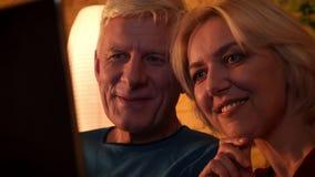 Seitenansichttrieb der Nahaufnahme des gealterten glücklichen Paars, das einen Film auf dem Laptop zuhause sitzt auf der Couch in stock footage