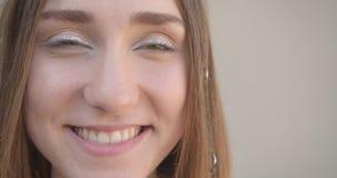 Seitenansichttrieb der Nahaufnahme des jungen hübschen kaukasischen weiblichen Gesichtes mit Haarringen und froh funkeln Make-up  stock footage