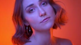 Seitenansichttrieb der Nahaufnahme der jungen attraktiven kaukasischen Frau mit dem Nasenpiercing, das Kamera mit Neonrot betrach stock video