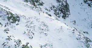Seitenantenne über schneebedecktem Berg des Winters mit den Bergsteigenskifahrerleuten, die herauf das Klettern gehen Schnee umfa stock video