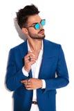 Seitenporträt des jungen eleganten Mannes, der seinen Ärmel repariert Lizenzfreie Stockbilder