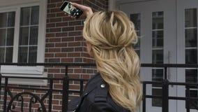 Seitenporträt eines schönen blonden Mädchens, das ein intelligentes Telefon zum Netz, selfies Fotos machend in einem Vorstadthaus stock video footage