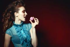 Seitenporträt eines schönen Modells mit kreativer Frisur und bunte bilden das Halten der violetten Makrone mit einem offenen Mund lizenzfreies stockbild