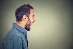 Seitenprofil des jungen verärgerten schreienden Mannes Stockfotografie