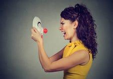 Seitenprofil einer verärgerten Frau, die an der glücklichen Clownmaske schreit Stockfotos