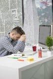 Seitenprofil geschossen vom frustrierten jungen Brünetteunternehmer, schreiend auf seinen Laptop im Büro und in den Klammern die  Stockfotografie
