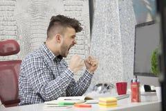 Seitenprofil geschossen vom frustrierten jungen Brünetteunternehmer, schreiend auf seinen Laptop im Büro und in den Klammern die  Stockbild