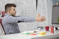 Seitenprofil geschossen vom frustrierten jungen Brünetteunternehmer, schreiend auf seinen Laptop im Büro und in den Klammern die  Lizenzfreie Stockfotografie