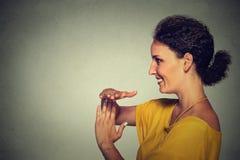 Seitenprofilporträt, Junge, die glückliche, lächelnde Frau, die Zeit heraus zeigt, gestikulieren Lizenzfreies Stockfoto