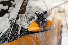 Seitenspiegel eines Autos säuberte in Selbstservice-Autowäschen stockbilder