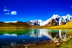 Seixos ake em uma costa com os céus azuis que refletem em águas ainda azuis paisagem Himalaia cênico fotos de stock royalty free