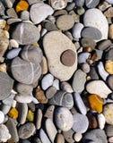 Seixos alisados na praia pelo mar Fotografia de Stock