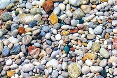 Seixos da cor sob a água do mar Imagens de Stock