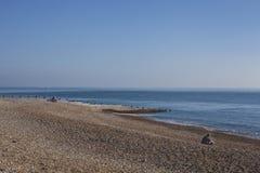 Seixos do leste de Eastbourne, Sussex na praia e nos céus azuis; dia ensolarado em outubro imagem de stock