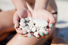 Seixos do mar nas mãos Imagens de Stock