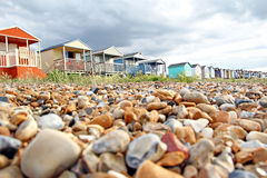 Seixos e cabanas da praia fotografia de stock royalty free