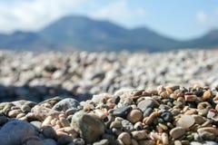 Seixos e escudos coloridos pequenos do mar contra a montanha e o céu borrados fotos de stock