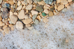 Seixos e espuma na praia, fim Fotos de Stock Royalty Free