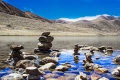 Seixos em uma água imóvel de um lago com reflexão do céu azul e das montanhas foto de stock royalty free