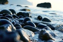 Seixos molhados no close up da costa de mar Imagem de Stock