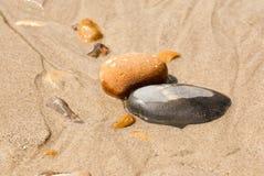 Seixos na central da areia Fotos de Stock