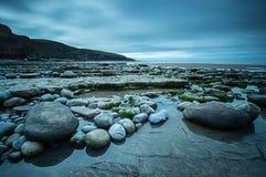 Seixos na costa na baía de Dunraven Fotos de Stock Royalty Free