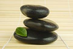 Seixos pretos do zen e folha verde no bambu imagem de stock