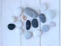 Seixos redondos cinzentos e brancos do mar na tabela de madeira com uma parte de shell Fotos de Stock