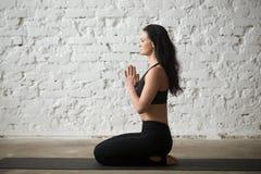 seiza姿势的年轻信奉瑜伽者妇女与namaste,顶楼背景 免版税库存图片