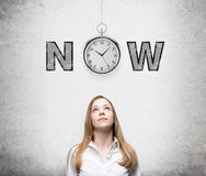 Seize the moment. A young woman looking up thinking about present opportunities and time. A pocket watch and the word 'now' over her head. Concrete background royalty free stock photos