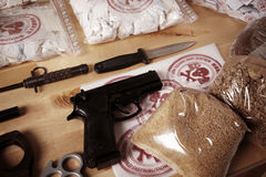 Seized collection of drugs and weapons. Drug packages, raw opium, drug dozens and weapons seized by police Royalty Free Stock Image