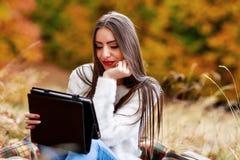 Seizoen, technologie en mensenconcept - jonge vrouw met tablet Royalty-vrije Stock Afbeelding
